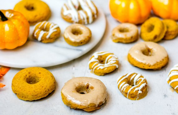 pumpkin donuts on white table with pumpkins and fall leaves