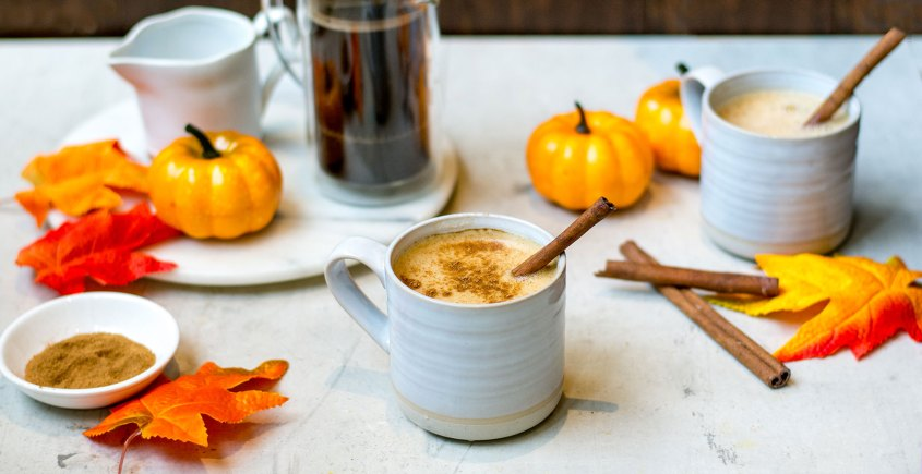 pumpkin spice latte with pumpkins and fall leaves in background