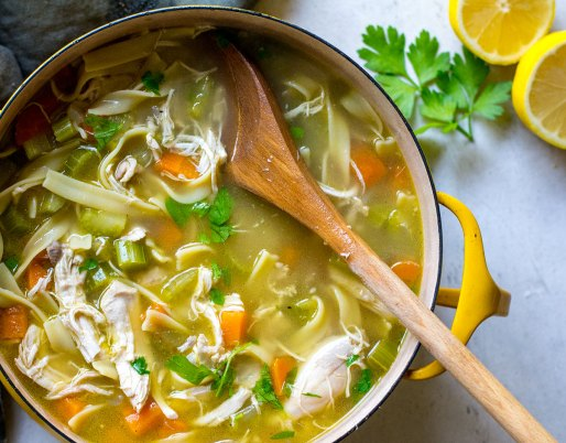 chicken noodle soup in pot with large spoon