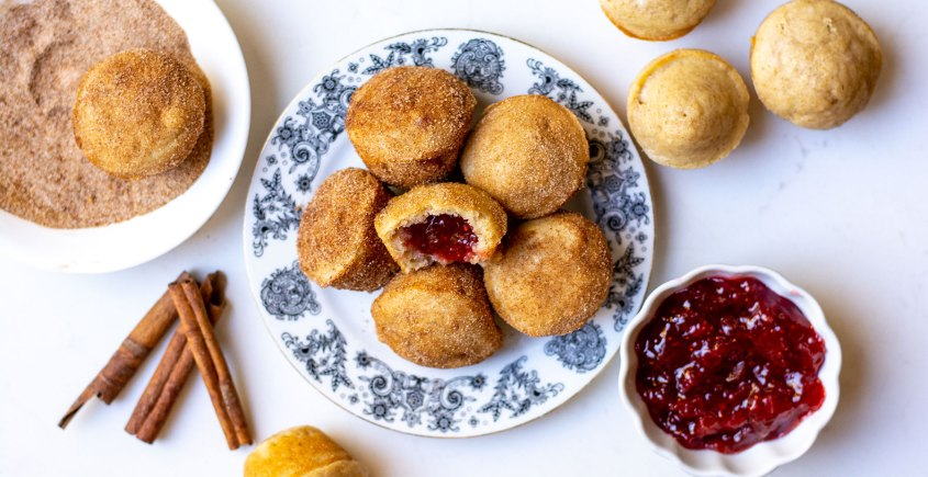 image of jelly donut muffins on plate with jam and cinnamon sticks