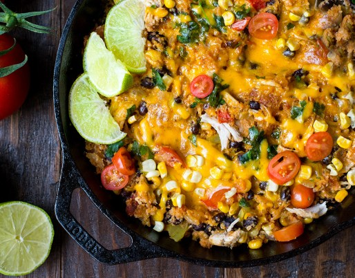 tex mex rice in cast iron pot with limes and tomatoes