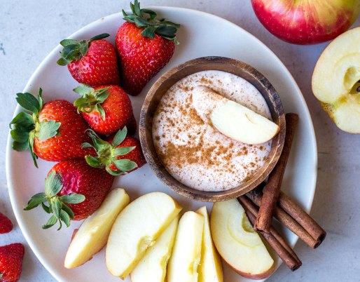 Cinnamon yogurt dip with strawberries and apple slices on plate.