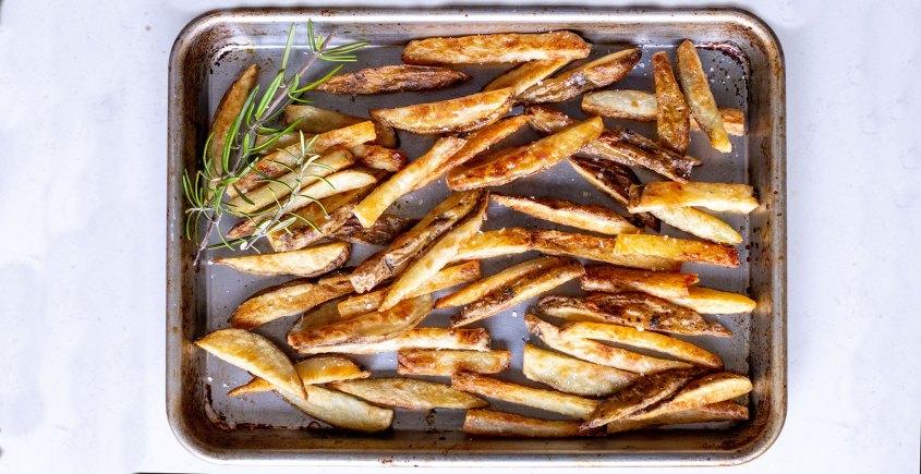 crispy baked fries on baking tray with rosemary