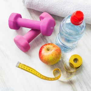 Workout-weights-Water-bottle-Apple-measuring-tape-on-white-surface