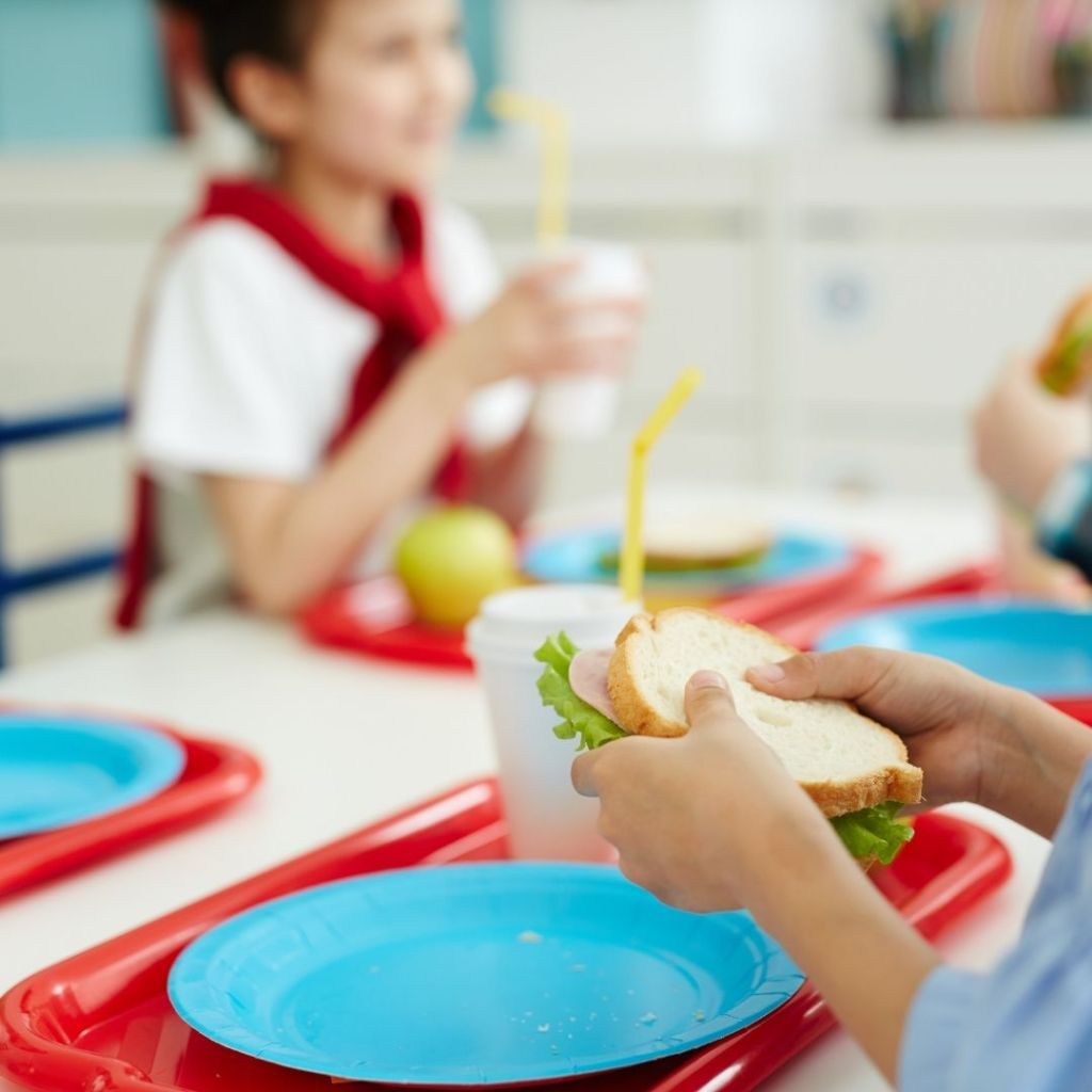 lunch-ideas-for-kids-concept-adult-sitting-with-child-at-table-eating-a-sandwich