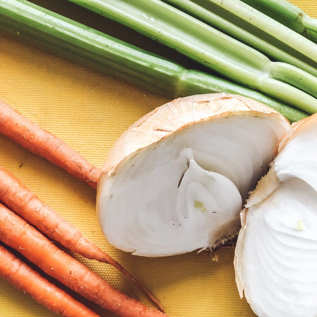 whole-celery-onion-carrot-on-yellow-cutting-board