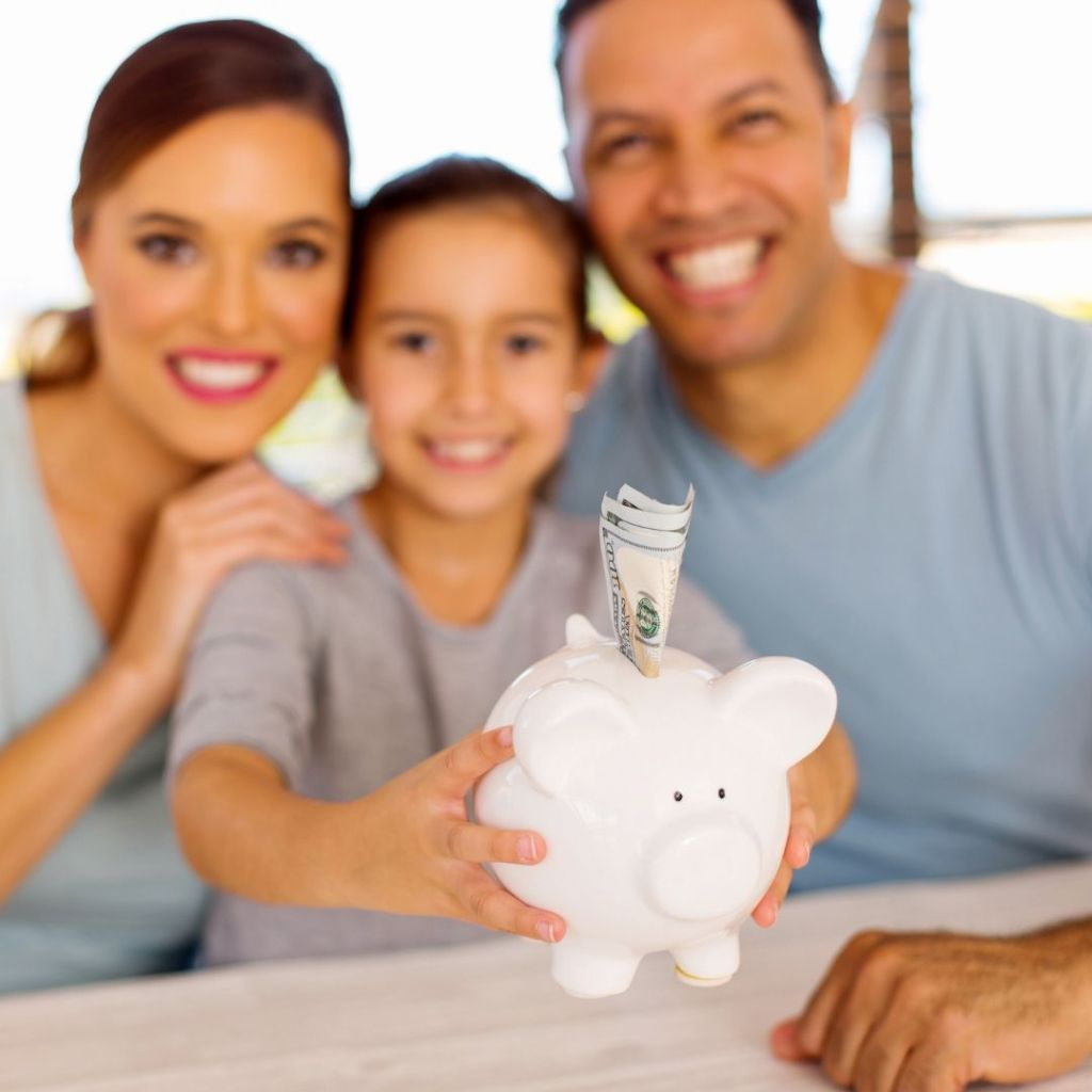 mom-dad-daughter-sitting-at-table-behind-piggy-bank