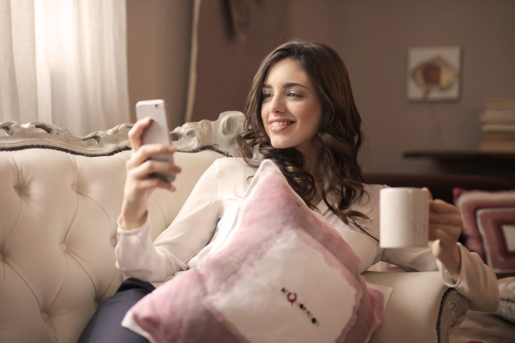 woman-holding-phone-on-sofa
