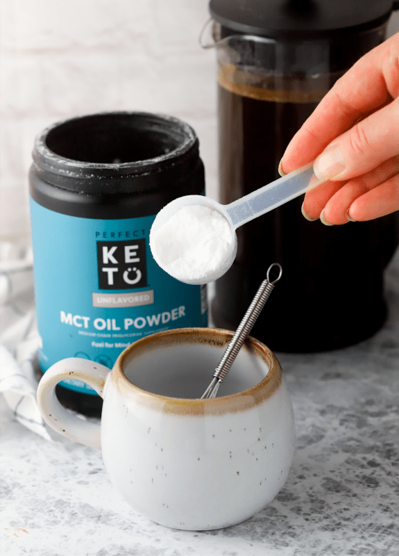 adding a scoop of vegan keto coffee creamer to a coffee cup