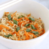 a bowl of vegan kelp noodle pad thai with sesame seeds carrots and scallions