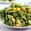 a plate of low carb vegan keto kale caesar salad with dressing, lupini beans and faux parm