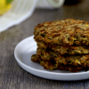 a plate of stacked zucchini fritters, surrounded by ingredients