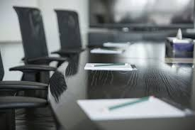 chairs at a boardroom-style table with blank notepads