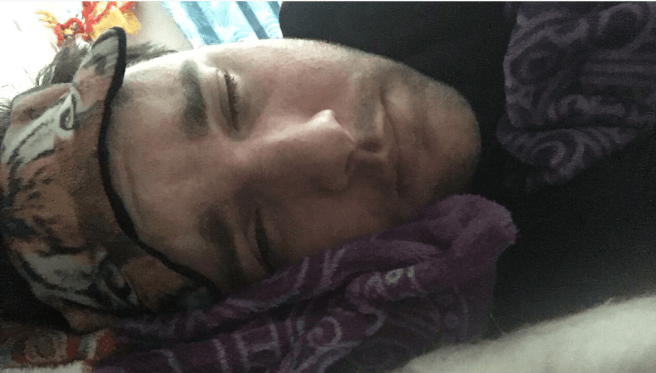Andrew lying down, wearing eye mask on forehead, eyes closed