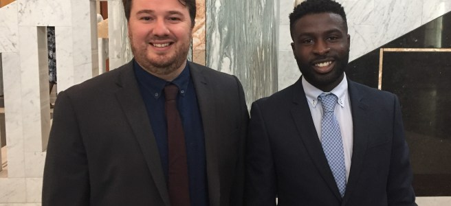 Dr Christopher Armstrong and Fane Mensah standing together, wearing suits and ties,