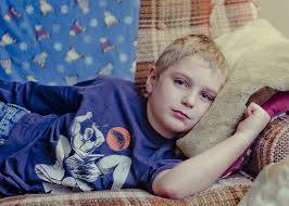 young boy in blue t-shirt lying on a couch with head on a cushion looking pale and unwell