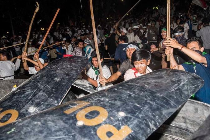 Sejumlah orang memukul petugas kepolisian saat unjuk rasa empat November di Jakarta, Jumat (4/11) malam. Aksi menuntut pemerintah untuk mengusut dugaan penistaan agama berakhir bentrok. ANTARA FOTO/M Agung Rajasa
