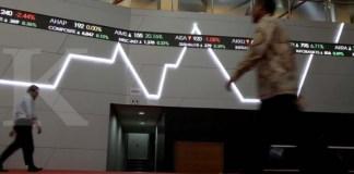 Pejalan kaki melintas dekat papan grafik digital pergerakan saham di pasar modal Bursa Efek Indonesia, Jakarta, Rabu (8/11). Pada penutupan perdagangan bursa Rabu (8/11), investor asing melakukan aksi jual bersih (net sell) sebesar Rp 819,05 miliar rupiah. Dalam sepekan terakhir, uang panas milik asing yang hengkang dari pasar saham mencapai Rp 5,6 triliun. KONTAN/Cheppy A. Muchlis/08/11/2017