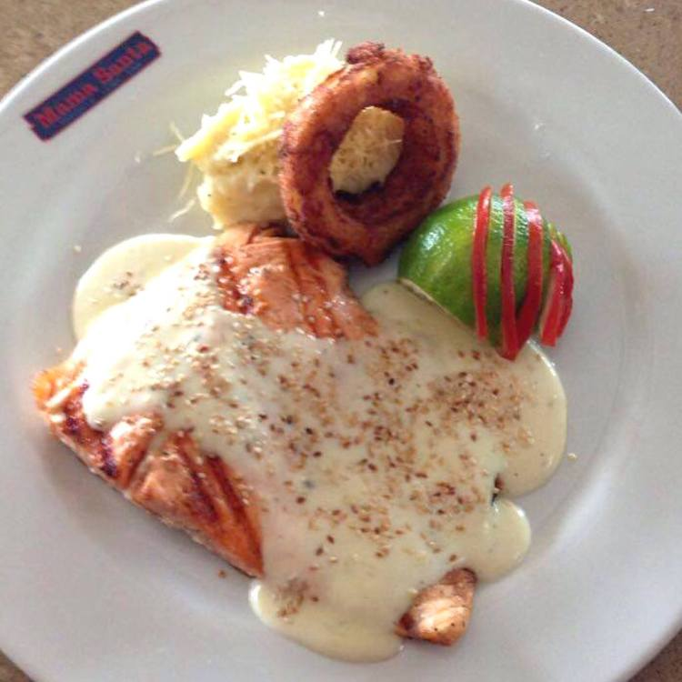 Grilled salmon with Béchamel Sauce, parmesan cheese and egg with mashed potatoes and onion rings, photo courtesy of Mama Santa