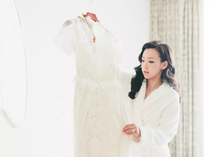 How to Preserve Your Wedding Dress Bride in robe looking at wedding dress