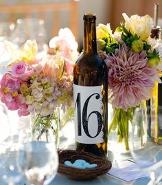 If your sticking w/ the wine corks for name settings...  thought this was cute for table #s!  (also you could have this wine available for drinking or do cut off the bottom and do the lights idea Jessa posted... Along with it being the table #!!!)  :D