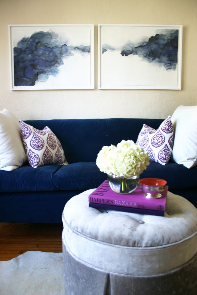 Blue velvet sofa, abstract watercolor painting, and a gray crushed velvet ottoman