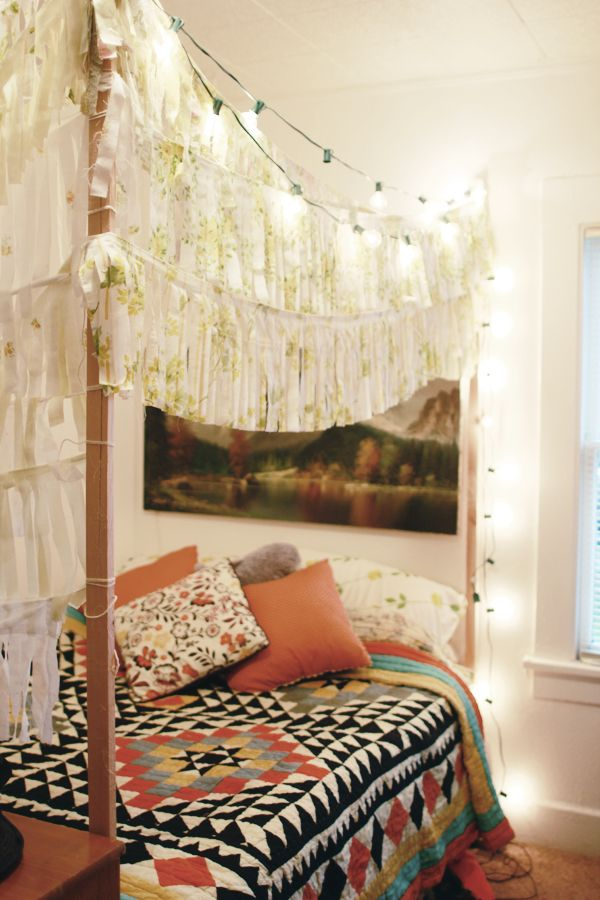 fringe canopy bed with geometric pattern blanket quilt and coral throw pillows, christmas lights -- modern bohemian boho interior design / vintage and mod mix with nature, wood-tones and bright accent colors / anthropologie-inspired chic mid-century home decor