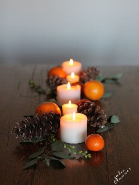 In just five minutes, you can create a gorgeous and simple tablescape by arranging pillar candles, pinecones, clementines, and floral stems.
