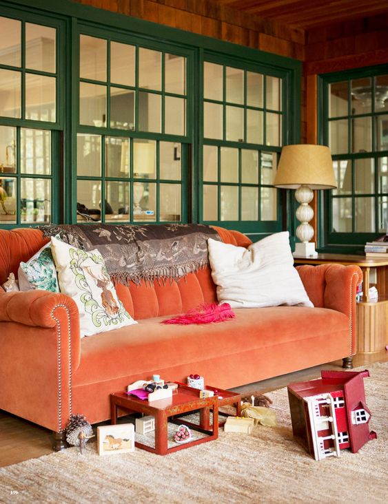 Beautiful Coral Velveteen sofa.  And the green windows are a great backdrop for it.