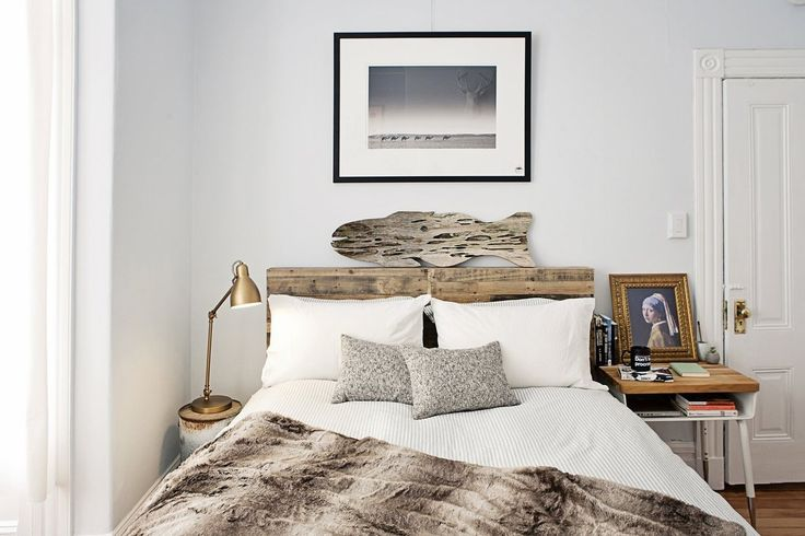 Jesse's Modern Bachelor Pad. Bed. Fur throw. Brass bedside task table lamp. Driftwood fish art. Great photograph with a hanging faux antler head reflected in it.