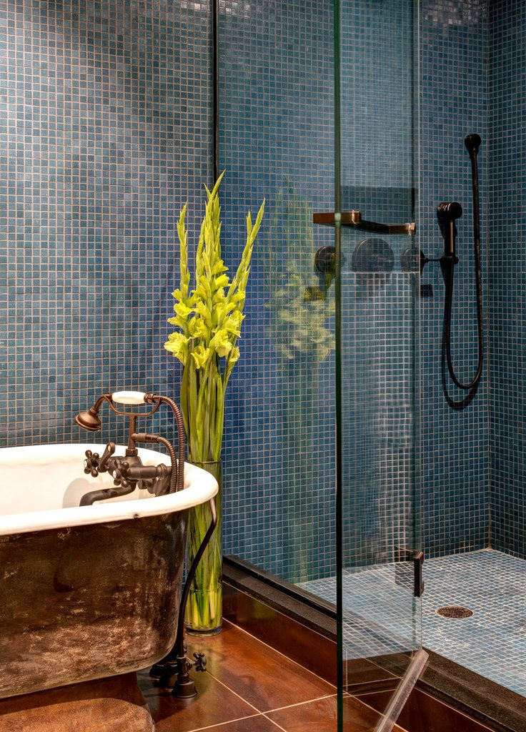 vintage cast-iron tub surrounded by glass mosaic tiles #bathroom