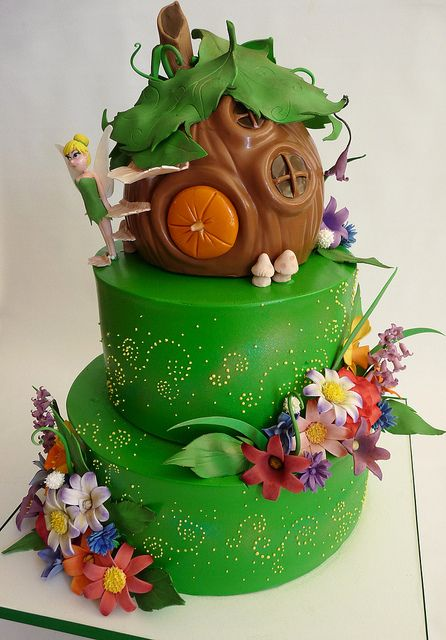 A Tinkerbell Theme: Tinker's house  buttercream bottom two tiers, fondant covered third tier. gumpaste hand painted flowers and accessories