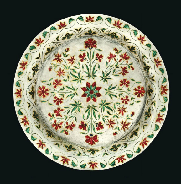 A Mughal enamelled and gold inlaid silver Dish, India, ca 1700  Of circular form with gently outward curving sides and a wide horizontal flat rim, composed of thick solid silver with gold inlaid outlines supporting red, emerald-green and dark blue enamel, composing radiating interior decoration floral sprays around a central rosette, the sides with scrolling vine and rim with flowering vine, areas of minor scratches to silver D. 22cm.