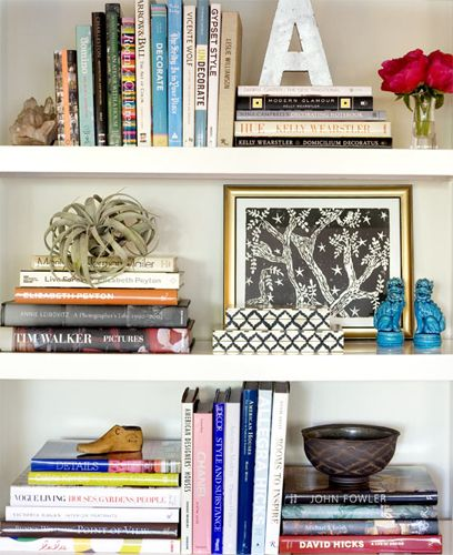 How to do a modern bookshelf, combining horizontal and vertical book displays, with natural elements, travel curios, and pottery.