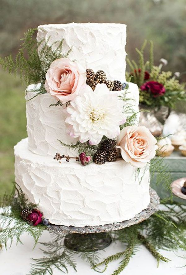 A three-tiered white wedding cake with textured buttercream and fresh flowers and berries by Elise Cakes | Brides.com