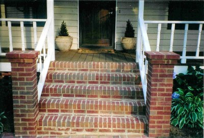 Brick front stoop with white vinyl rail