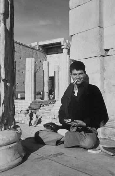 Beatnik poet Gregory Corso sitting in lotus position during visit to the Parthenon. Photo by Loomis Dean (Oct 1959)