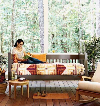 A screened-porch with a bed porch swing. Backyard porch design ideas and home decor