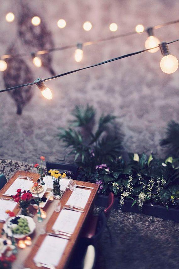 Guirnaldas de luces y manteles individuales, decoración perfecta para una cena con amigos.