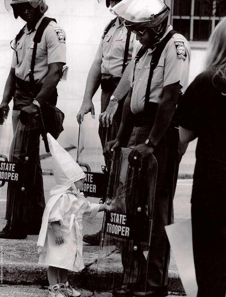 Ecco una Georgia State Trooper in tenuta antisommossa a una protesta KKK in una città a nord della Georgia negli anni '80.  Il Trooper è nero.  In piedi di fronte a lui e toccando il suo scudo è un curioso bambino vestito in un cappuccio Klan e accappatoio.