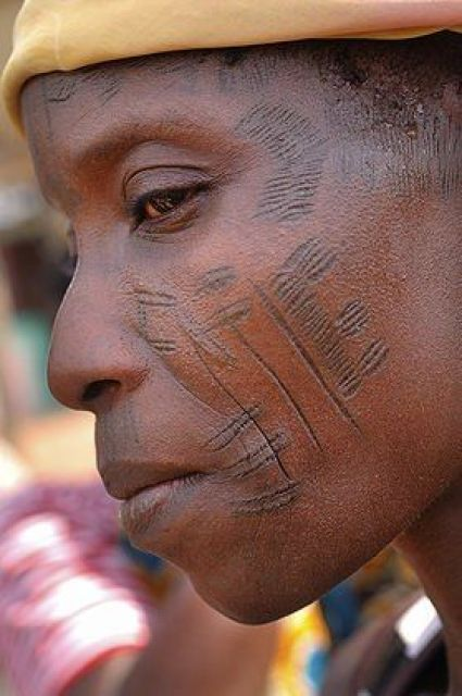 Africa | A woman shows the tribal scarification on her face. Scarification is used as a form of initiation into adulthood, beauty and a sign of a village, tribe and clan. Abomey-Calavi, Benin | © Jean-Michel Clajot