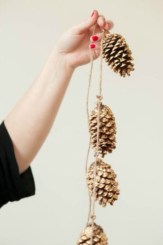 spray paint pine cones gold and string them