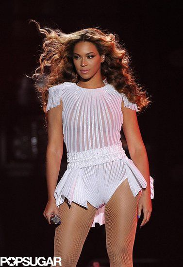 : Beyoncé looked out on her fans wearing a white, sheer striped leotard with nude fishnet tights — we especially love the fringed shoulder detail.