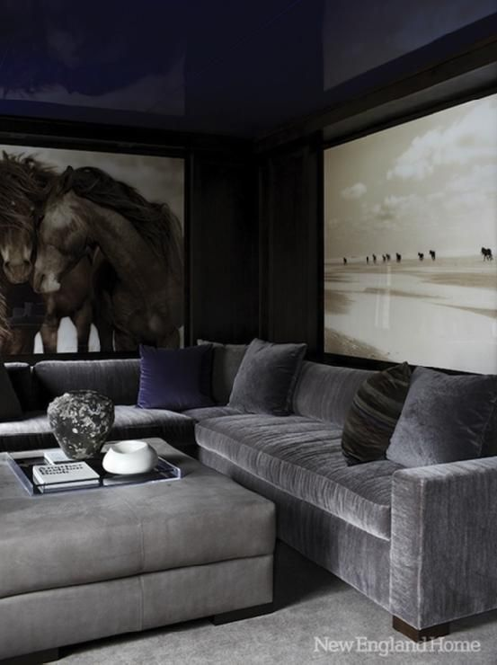 Fantastic media room with glossy blue lacquer walls ceiling, horse art, steel gray velvet sectional sofa and ottoman