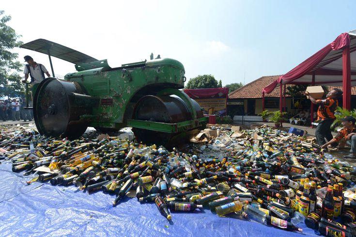Uno schiacciasassi distrugge bottiglie di alcol, Riviste pronografiche posta il video pirata Davanti alla Centrale di Polizia a Giacarta, Indonesia (ADEK BERRY / AFP / Getty Images)