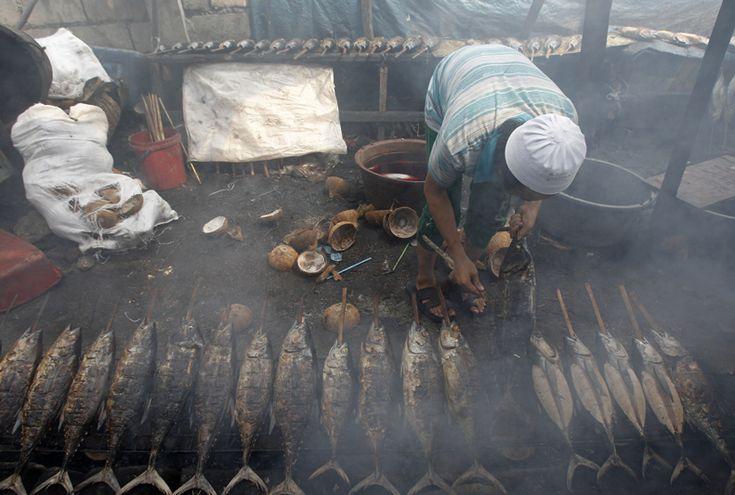 Un uomo cucina del pesce per venderlo in Un Mercato di Manila, Nelle Filippine, il 10 luglio.