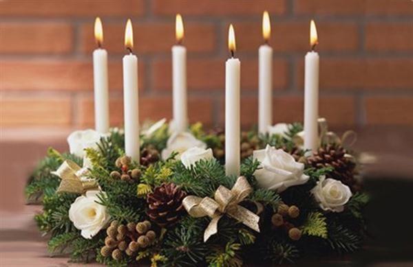 Новогодняя композиция из еловых веток со свечами, бантиками,  шишками, розами, брунией.