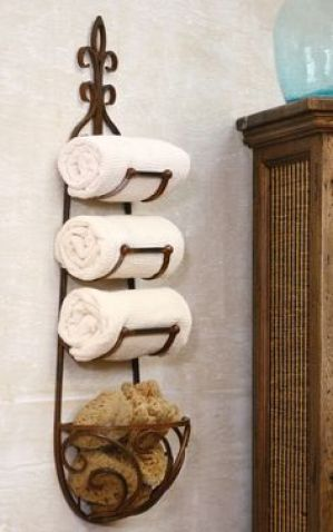 The rustic finish belies the artistry in this three slot towel rack complete with scrolled basket for artisanal soaps, bathing sponges or washcloths. Hand crafted in cottage industries abroad. brbr...