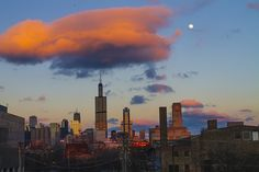 Hanging Around - Taken while riding home on the pink line. I was caught up in the large cloud directly above the Sears tower and the setting sun turning it pink. Over to the right the full moon is just starting to rise in the sky. - Señor Codo via flickr.com