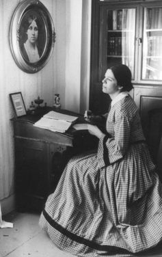 Louisa Mae Alcott sitting at the desk where she wrote